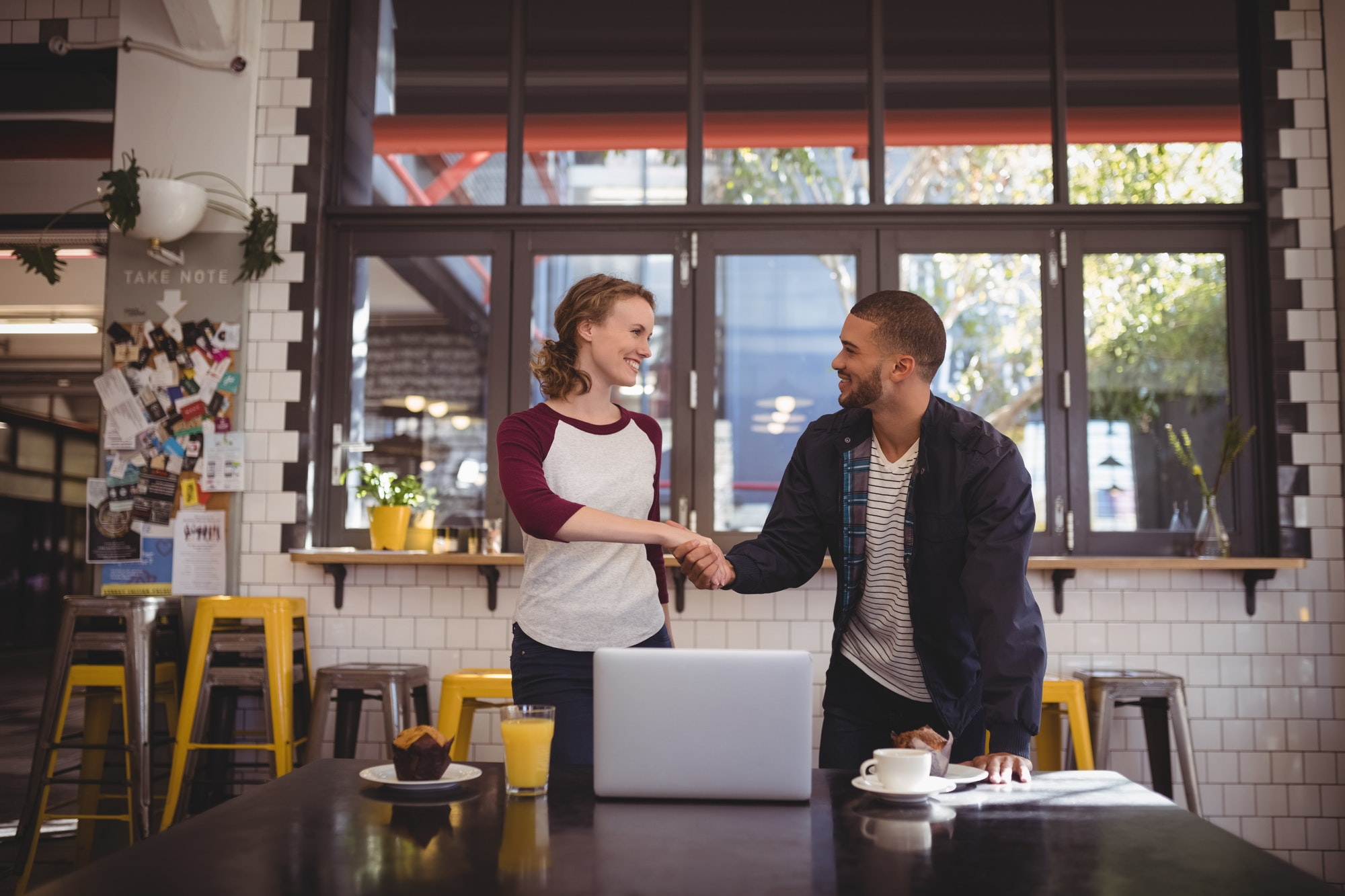 Smiling young man and woman shaking hands at coffee shop